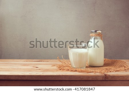 Milk bottle and milk glass on wooden table. Healthy eating concept