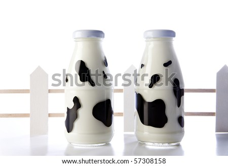 milk bottles with cow camouflage isolated on a white background