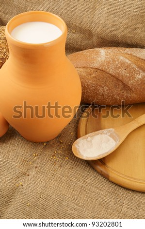 Milk, bread and spoon with flour on jute background