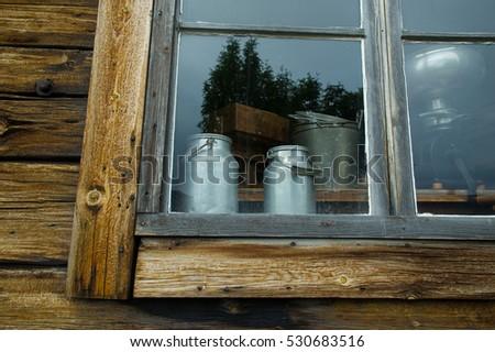 milk buckets in a window of an old farmhouse #530683516