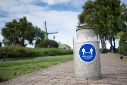 Milk can on a foothpath with blue social distancing sign HOUD AFSTAND. Translation Dutch text on sign: