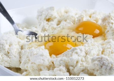 Milk cheese and eggs in a bowl.