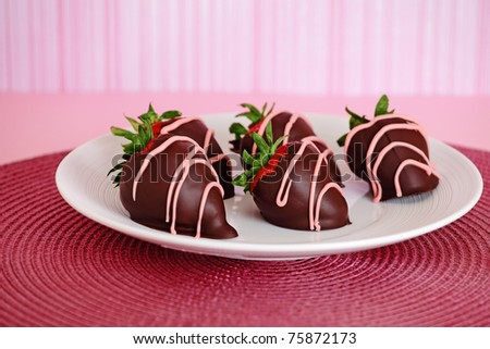 Milk chocolate dipped strawberries on a pink place mat