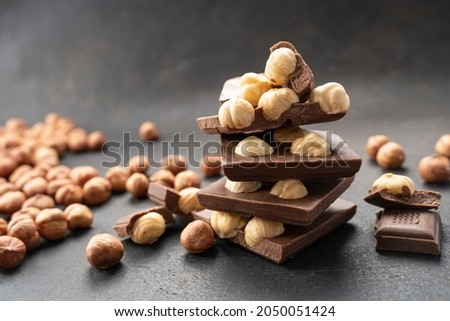 milk chocolates bars with nuts on black table. Hazelnut milk chocolate pieces tower close up. Sweet food photo concept. Chunks of broken chocolate. Confectionery craft for chocolate background