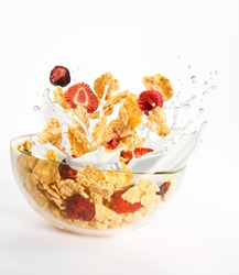 Milk, cornflakes and red dried fruits splash in a glass bowl on a white background