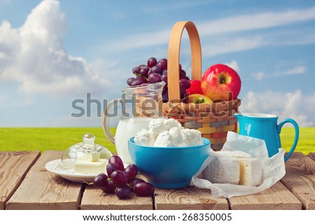Milk, cottage cheese, butter and fruit basket over meadow background. Jewish holiday Shavuot celebration
