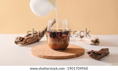 Milk cream pours into a transparent glass of black coffee on a minimalistic beige natural wooden background. Coffee drink cocktail with milk. Photo stock ©