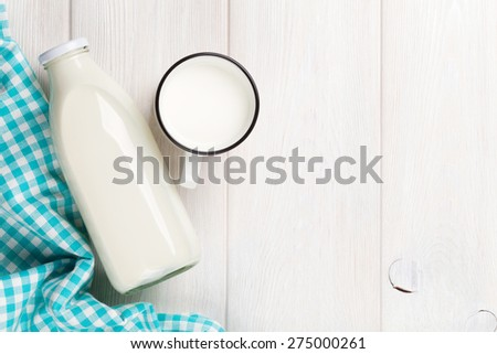 Milk cup and bottle on wooden table. Top view with copy space  #275000261