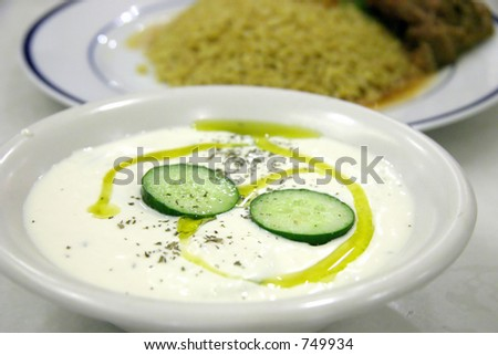 Milk curd yogurt dish with cucumber slices and olive oil with main course