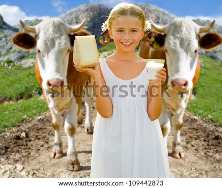 Milk fresh from the cow - lovely girl with dairy products and cows on mountains pasture