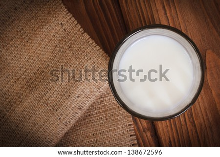 Milk in a glass on a wooden table  top view