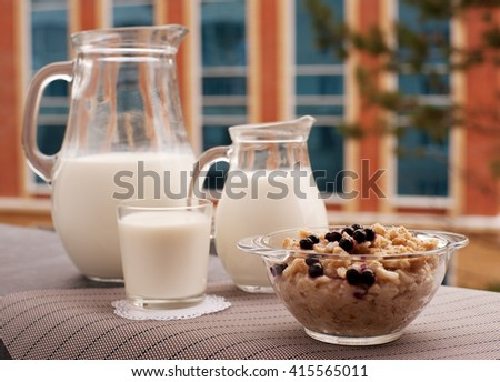 Milk in a jug with porridge on the balcony. The most useful breakfast is oatmeal and milk. Porridge is rich in fiber. Milk contains calcium. The morning will be cheerful.