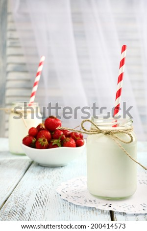 Milk in bottles with paper straws on table