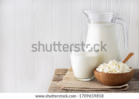 milk in glass and jug with cottage cheese in bowl on white wooden background Foto stock ©