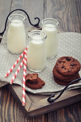 Milk in small jars with striped straws and cookies on vintage tray