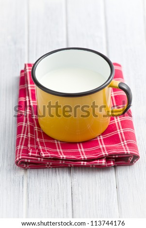 milk in tin mug on wooden table