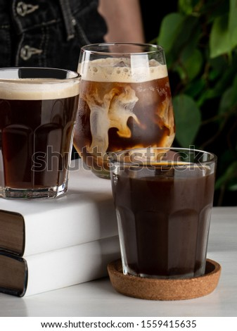 Milk is swirling and splashing in a glass of iced latte  #1559415635