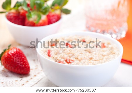 Milk porridge with slices of fresh strawberries, berries in the background