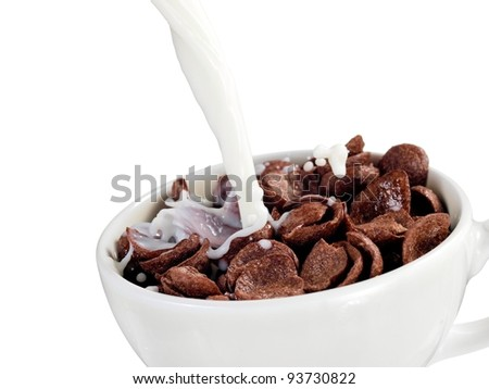 Milk pouring into a cup with chocolate cereal flakes