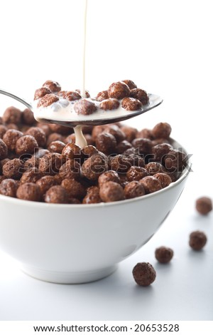 milk pouring into bowl with chocolate balls isolated