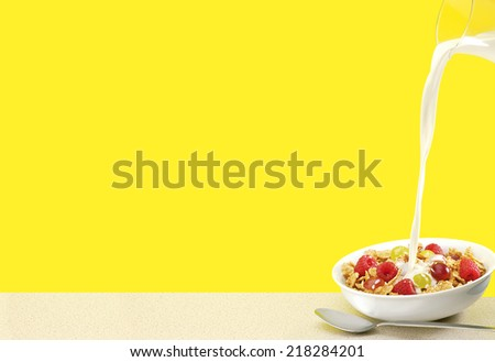Milk pouring into breakfast bowl with spoon