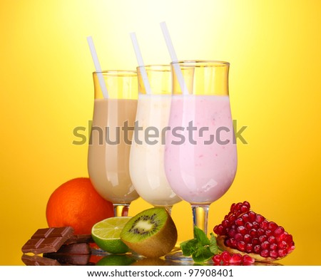 Milk shakes with fruits and chocolate on yellow background