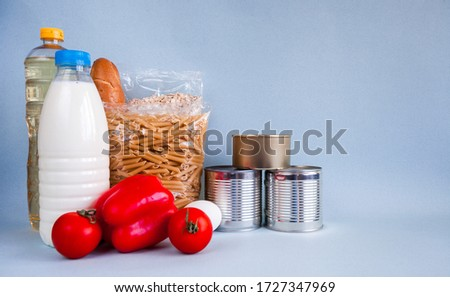 Photo of Milk, sunflower oil, canned food, pasta, red pepper, two tomatoes and a white egg on a background of marine color. Free space on the right.