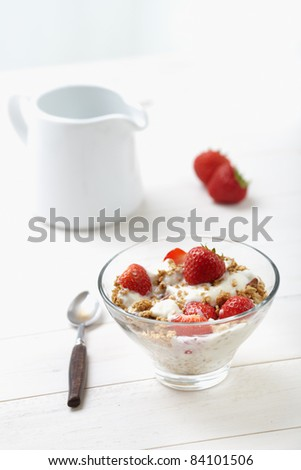 Milk with cereal and strawberries on a white table, country style
