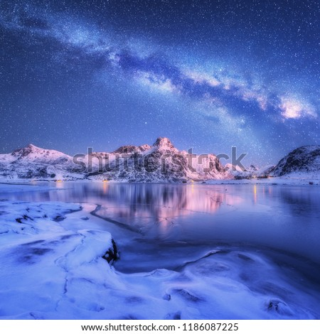 Milky Way above frozen sea coast and snow covered mountains in winter at night in Lofoten Islands, Norway. Arctic landscape with blue starry sky,  water, ice, snowy rocks, milky way. Beautiful space #1186087225