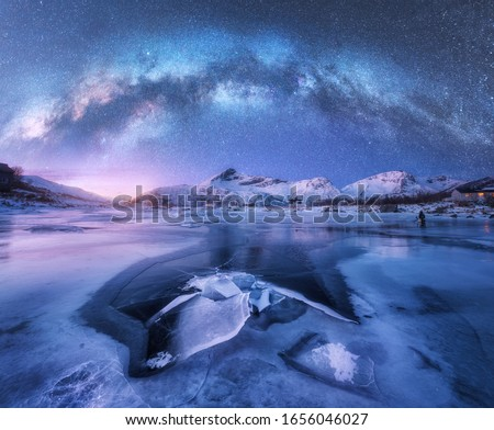 Milky Way above frozen sea coast and snow covered mountains in winter at night in Lofoten Islands, Norway. Arctic landscape with blue starry sky,  water, ice, snowy rocks, milky way. Space and galaxy