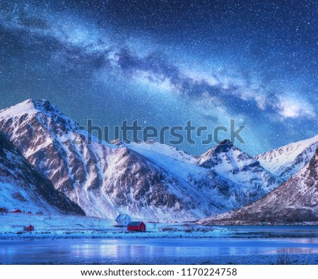 Milky Way above houses and snow covered mountains in winter at night. Starry sky, small village, snowy rocks in Lofoten Islands, Norway. Nordic landscape with milky way, water, ridge, buildings. Space