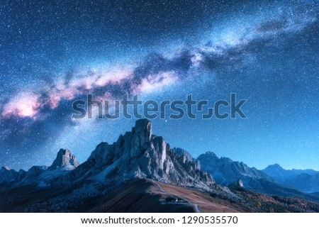Milky Way above mountains at night in autumn. Landscape with alpine mountain valley, blue sky with milky way and stars, buildings on the hill, rocks. Aerial view. Passo Giau in Dolomites, Italy. Space #1290535570