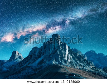 Milky Way above mountains at night in summer. Landscape with alpine mountain valley, blue sky with milky way and stars, buildings on the hill, rocks. Aerial view. Passo Giau in Dolomites, Italy. Space #1340126060