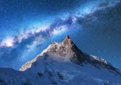 Milky Way above snowy mountains. Space. Fantastic view with snow covered rocks and starry sky at night in Nepal. Mountain ridge and sky with stars in Himalayas. Landscape with bright milky way. Galaxy