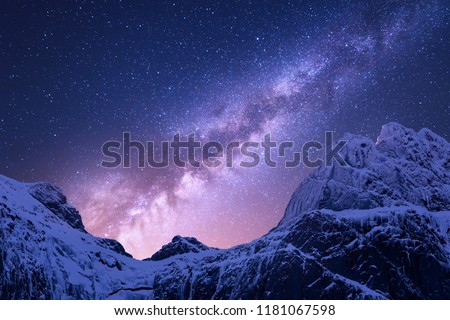 Milky Way above snowy mountains. Space. Fantastic view with snow covered rocks and starry sky at night in Nepal. Mountain ridge and sky with stars in Himalayas. Landscape with purple milky way. Galaxy