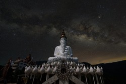 Milky Way above the Giant white Buddha statue in the night at Phra That Pha Son Kaew Temple landmark of Phetchabun province unseen Thailand.