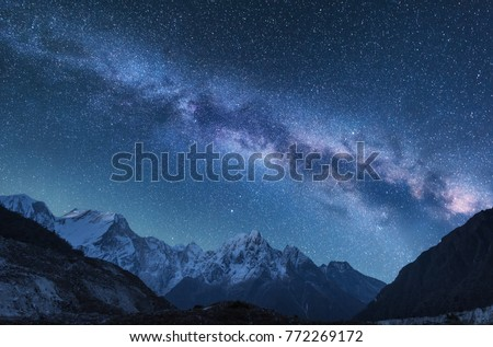 Milky Way and mountains. Amazing scene with himalayan mountains and starry sky at night in Nepal. Rocks with snowy peak and sky with stars. Beautiful Himalayas. Night landscape with bright milky way #772269172