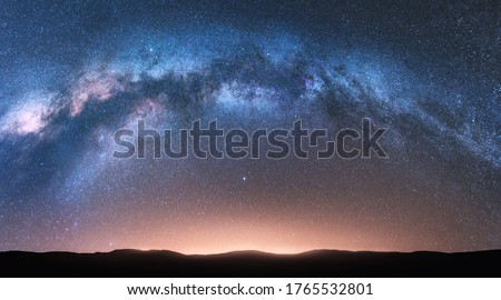 Milky Way arch. Fantastic night landscape with bright arched milky way, sky with stars, yellow sunlight and hills. Beautiful scene with universe. Space background with starry sky. Galaxy and nature Photo stock ©