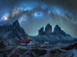 Milky Way arch over mountains at starry night in summer. Landscape with alpine mountains, building, church, sky with arched milky way and stars, high rocks. Tre Cime in Dolomites, Italy. Space
