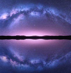 Milky Way arch reflected in water. Night landscape with bright arched milky way, purple sky with stars, lake, pink light and hills. Beautiful space background with starry sky. Galaxy and nature