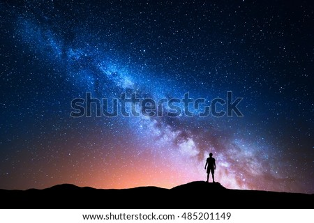 Milky Way. Beautiful night sky with stars and silhouette of a standing alone man on the mountain. Blue milky way and man on the hill. Background with galaxy and silhouette of a man. Universe