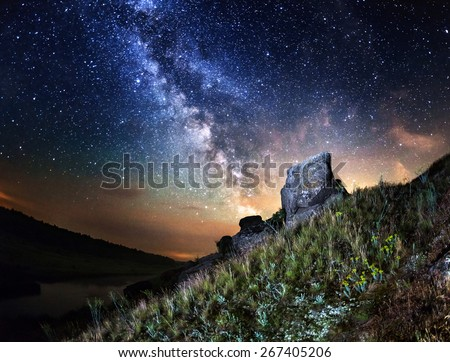 Milky Way. Beautiful summer night sky with stars, rocks, trail and green plants in Ukraine