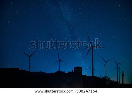 Stock Photo Milky way behind a windmill farm.