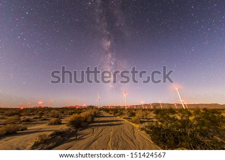 Stock Photo Milky way behind a windmill farm in the desert.