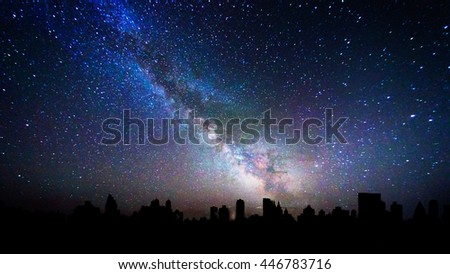 Milky way galaxy over a city skyline silhouette #446783716