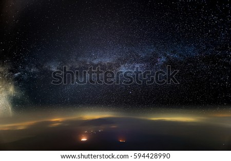 Milky Way Galaxy seen above horizon, atmosphere of earth with mountains covered in flowing clouds, long exposure photography. #594428990