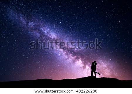 Milky Way. Night landscape with silhouettes of hugging and kissing man and woman on the mountain. Colorful sky with stars. Silhouette of lovers. Couple, relationship. Milky way with people. Universe