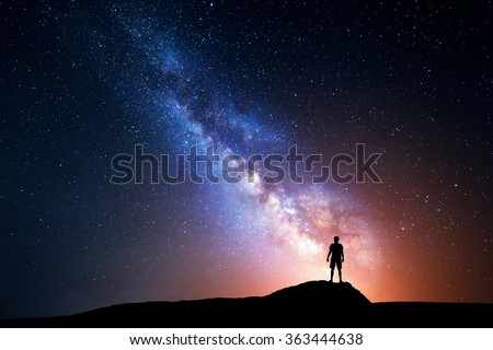 Milky Way. Night sky with stars and silhouette of a standing happy man with yellow light. Space background