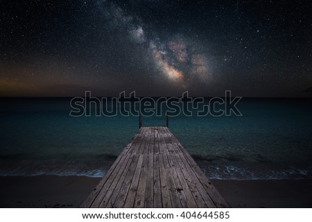 Stock Photo Milky way over che seashore and small wooden jetty in perspective
