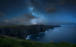 Milky way over dramatic Cliffs of Moher and wild Atlantic Ocean, Ireland.